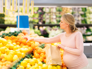 pregnant woman with bag buying oranges at grocery
